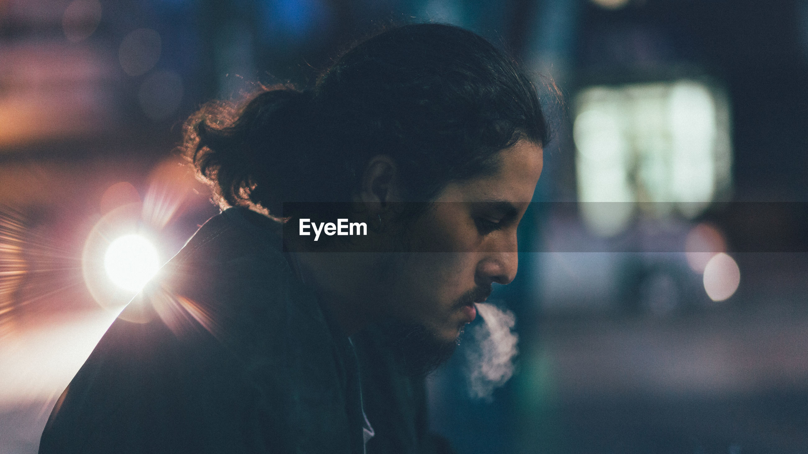 Profile view of man smoking in city at night