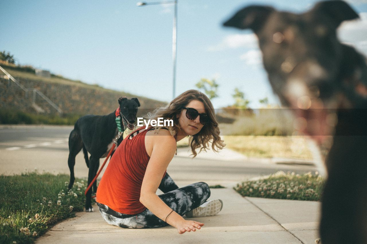 Portrait Of Young Woman With Dog On Road
