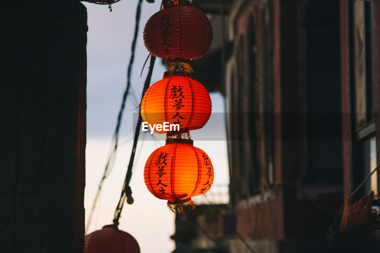 Low Angle View Of Illuminated Chinese Lanterns Hanging Amidst Buildings