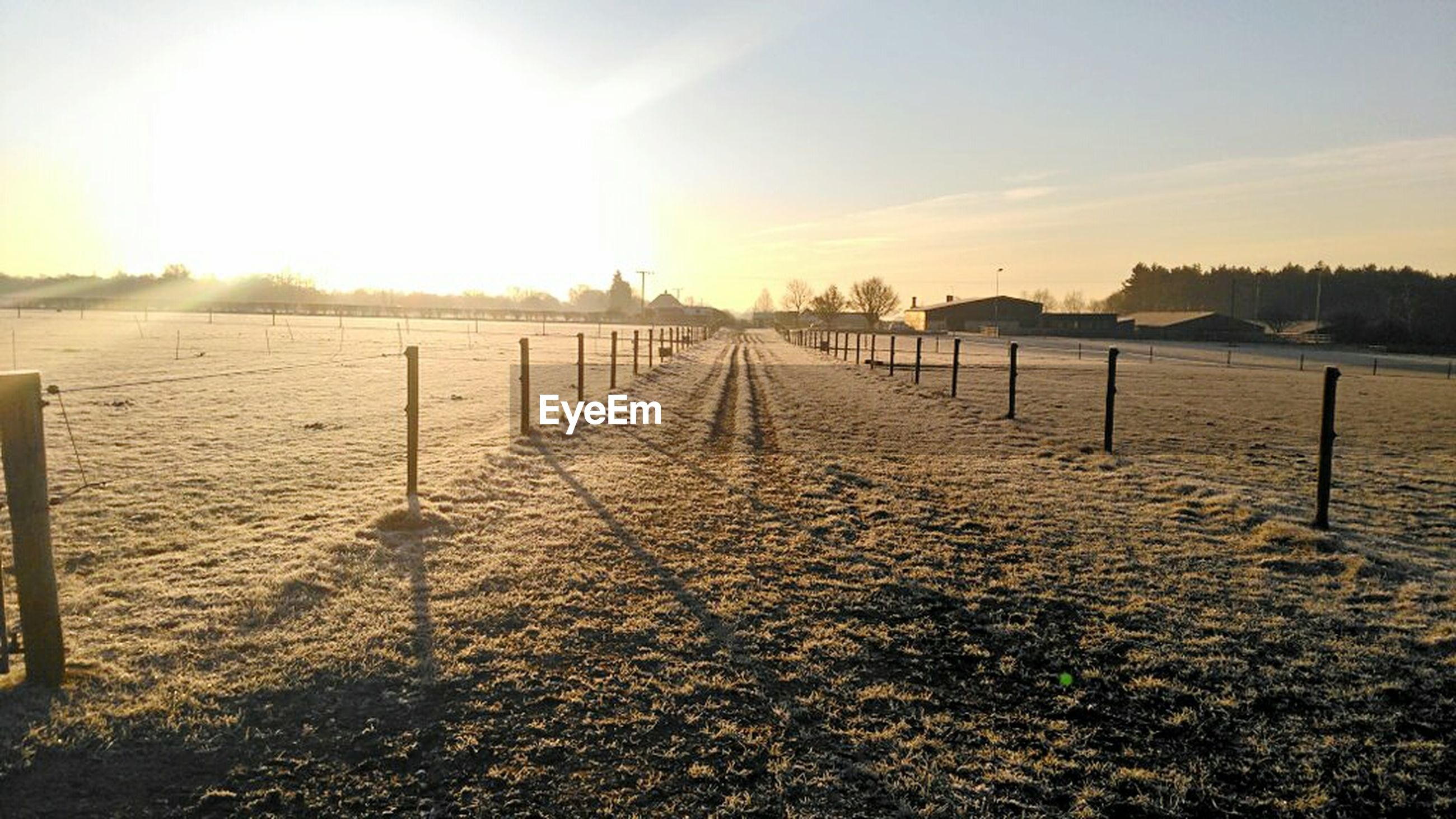 sunset, sun, tranquil scene, tranquility, sunlight, scenics, sky, beauty in nature, water, nature, idyllic, fence, sea, wooden post, the way forward, sunbeam, landscape, outdoors, beach, diminishing perspective