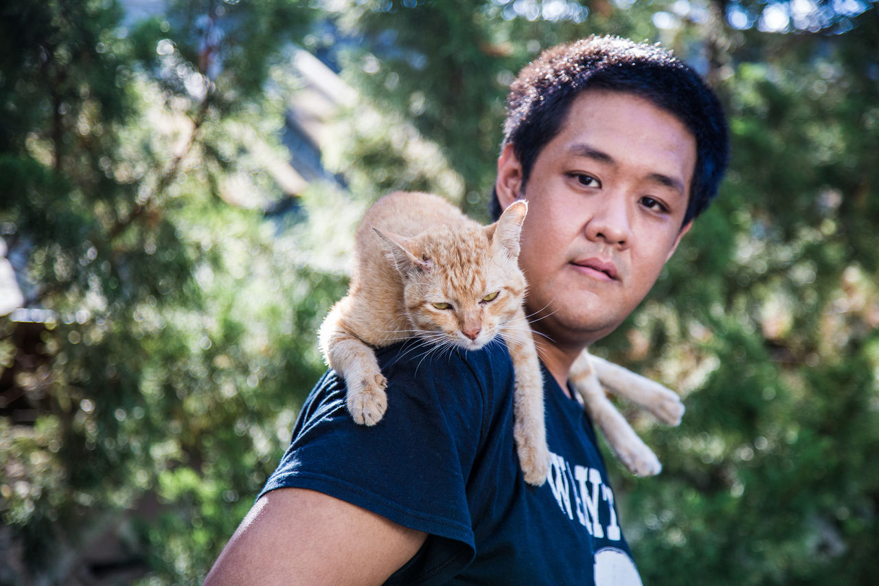 Portrait of asian man with cat on shoulder