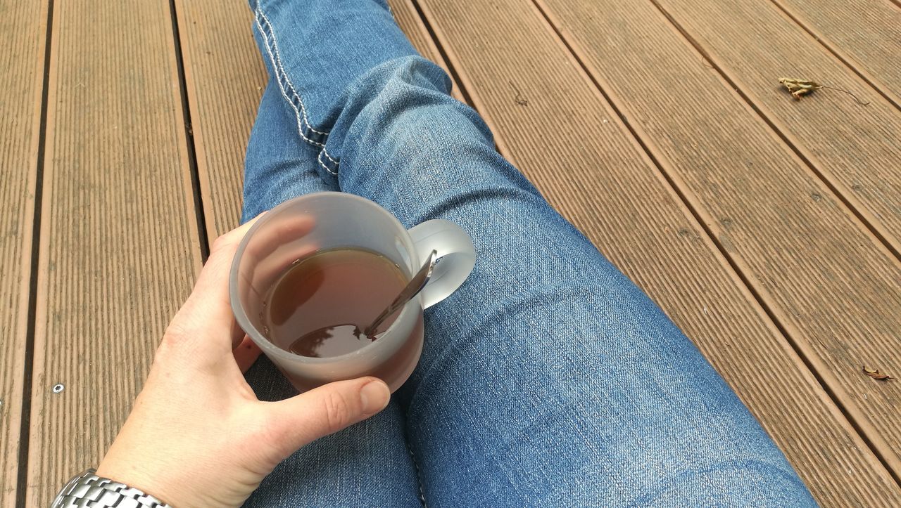 cup, mug, drink, one person, holding, coffee, jeans, human body part, coffee - drink, human hand, refreshment, coffee cup, lifestyles, food and drink, casual clothing, hand, real people, personal perspective, low section, hot drink, body part, drinking, tea cup