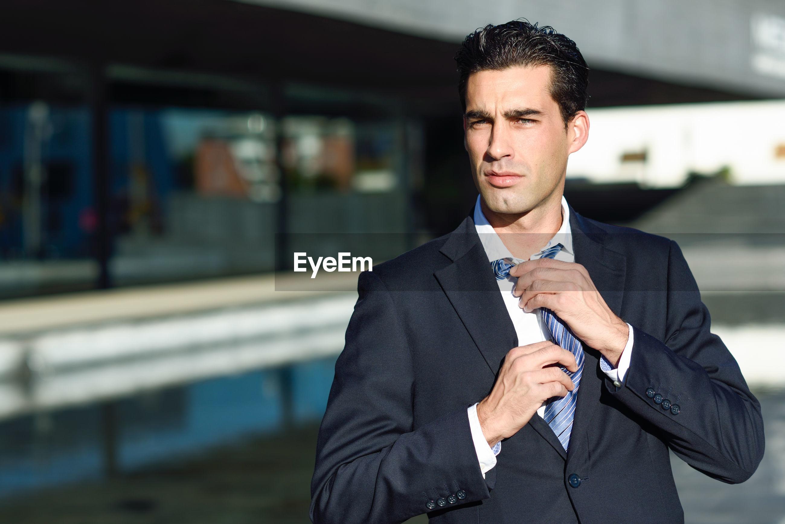 Portrait of businessman adjusting tie