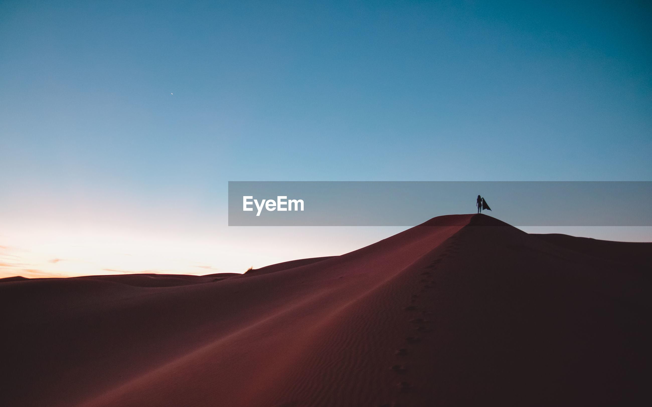 Desert against blue sky during sunset