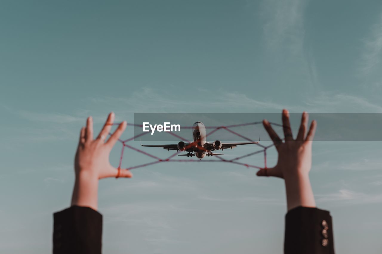 Cropped hands holding string against airplane flying in sky