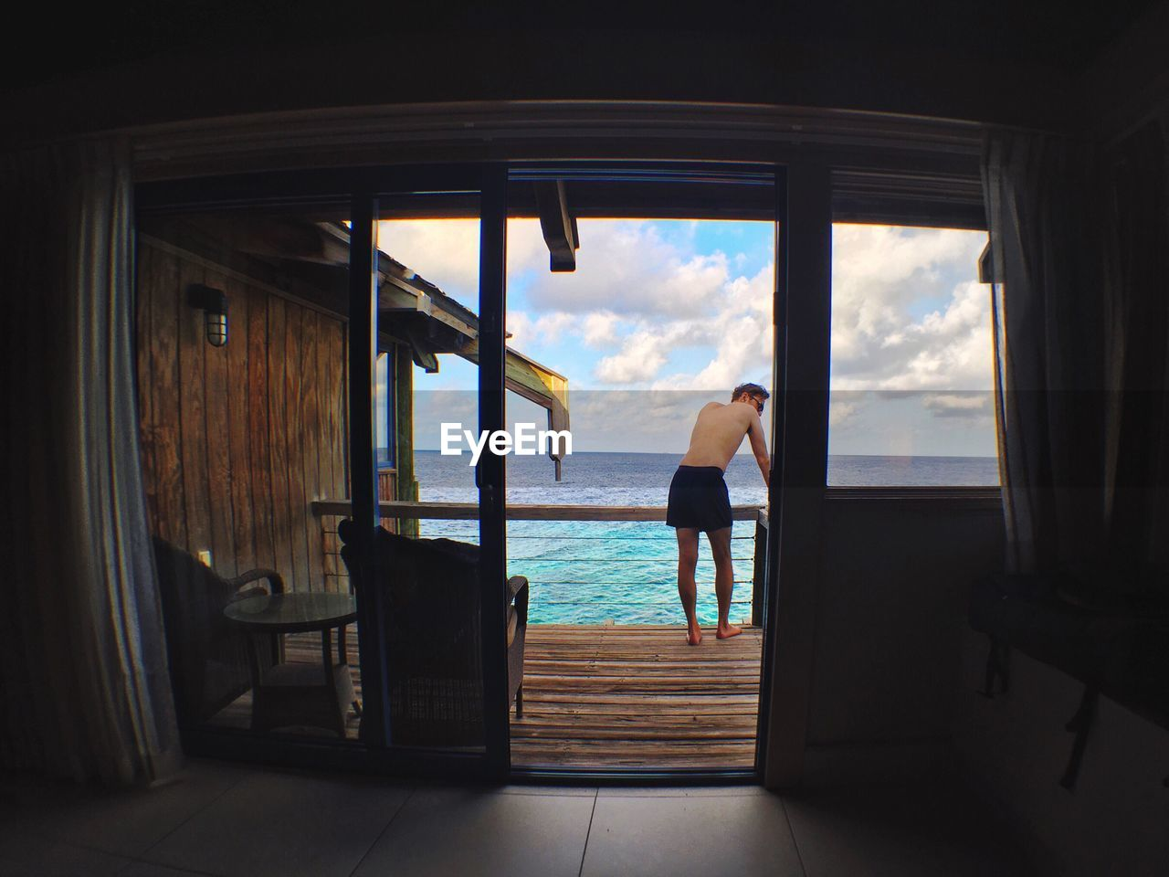 sea, water, sky, full length, one person, window, looking at view, day, standing, horizon over water, leisure activity, chair, cloud - sky, real people, nature, vacations, wood - material, indoors, looking through window, scenics, nautical vessel, beauty in nature, luxury hotel, architecture, men, young adult, people
