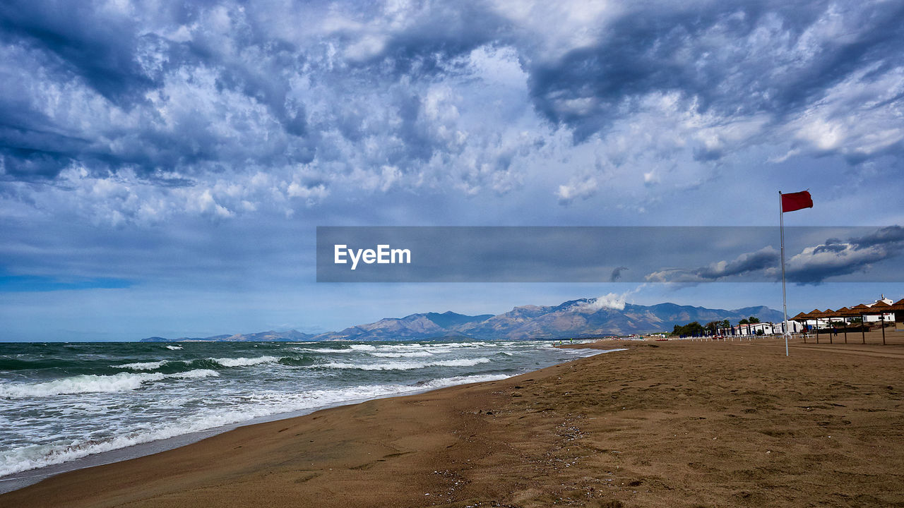 beach, sea, cloud - sky, sky, land, water, sand, beauty in nature, scenics - nature, flag, nature, horizon over water, day, horizon, tranquil scene, tranquility, wave, incidental people, sign, outdoors