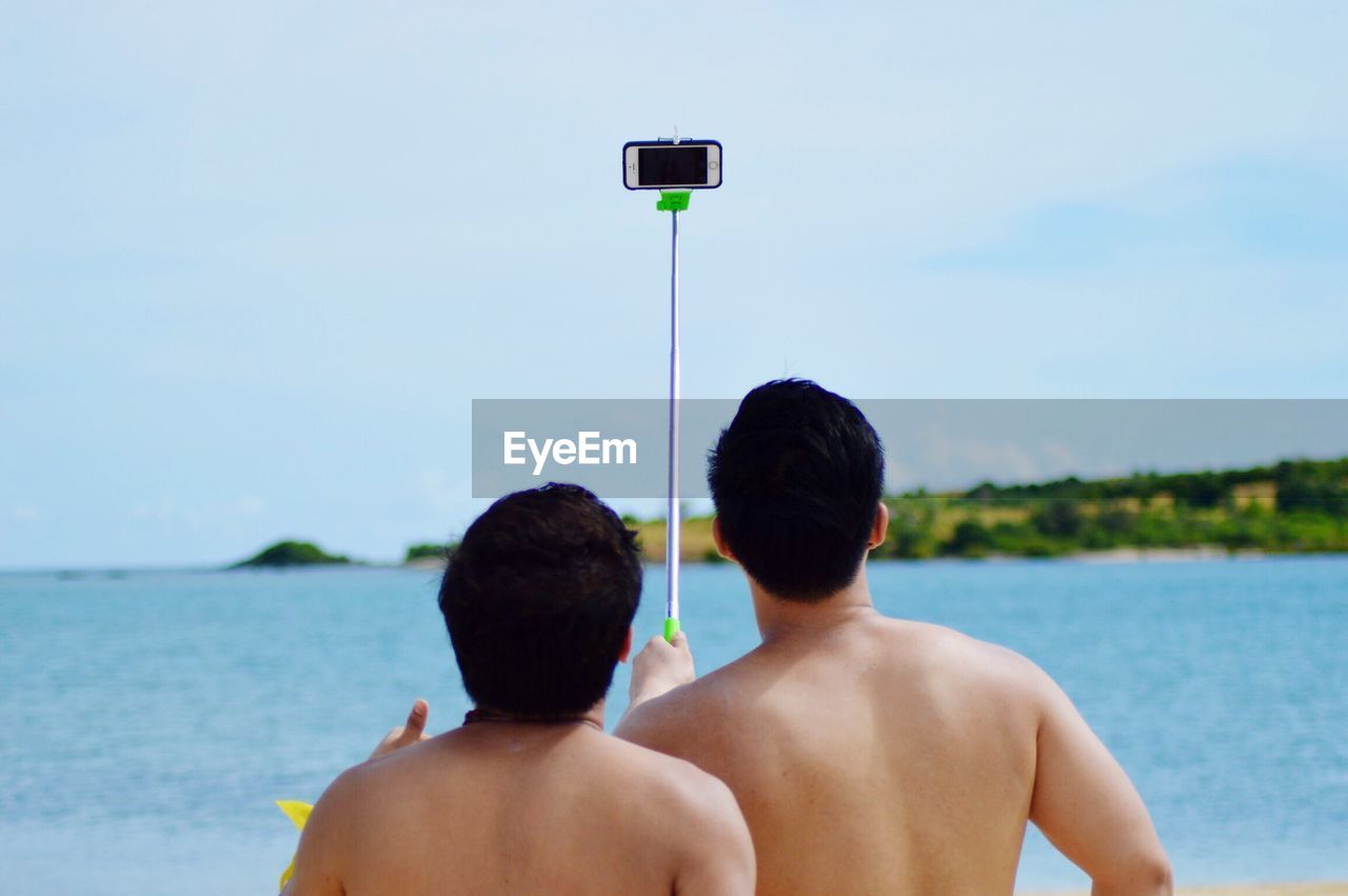 Rear View Of Shirtless Friends Taking Selfie At Beach Against Sky