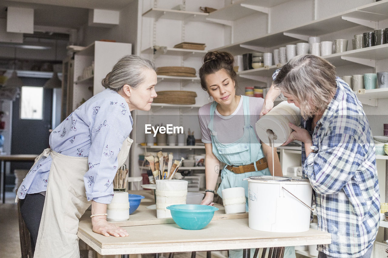 group of people, indoors, togetherness, women, adult, childhood, kitchen, real people, lifestyles, child, people, females, males, casual clothing, standing, preparation, domestic room, men, mid adult