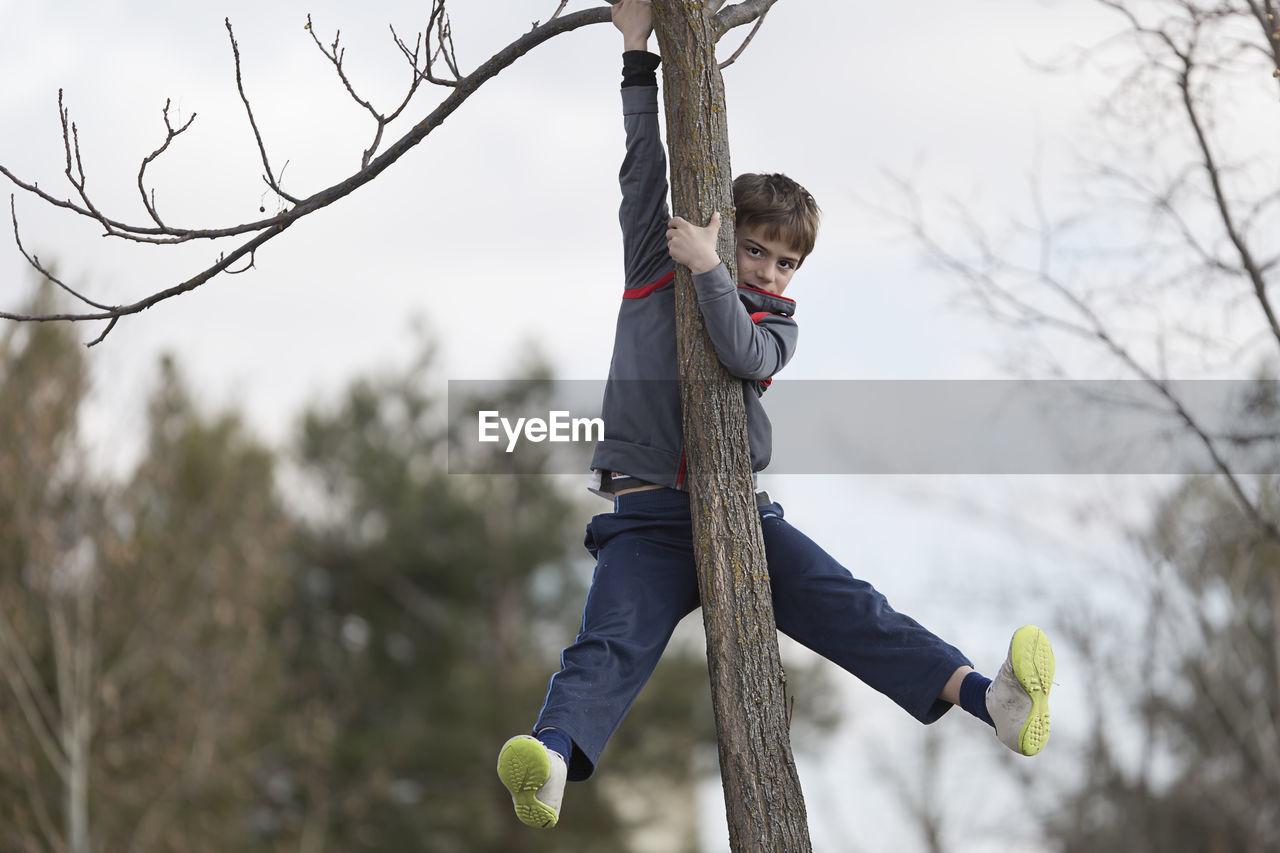 Full Length Portrait Of Boy Climbing Tree Against Sky