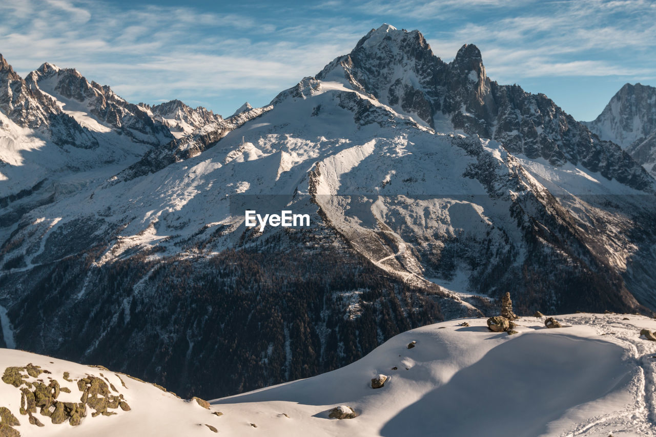 snow, cold temperature, mountain, winter, scenics - nature, beauty in nature, mountain range, snowcapped mountain, tranquil scene, nature, tranquility, sky, environment, covering, day, non-urban scene, sunlight, cloud - sky, landscape, no people, mountain peak, outdoors, formation, powder snow