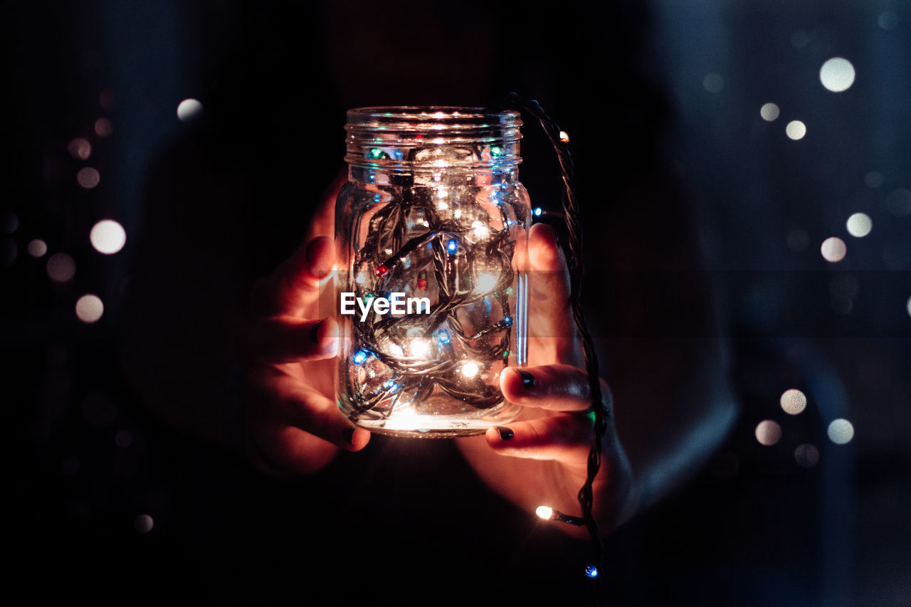 Woman holding illuminated fairy lights in jar during christmas