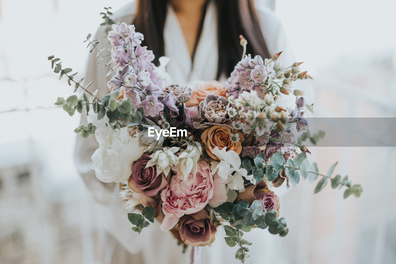 Midsection Of Woman Holding Bouquet While Standing Outdoors