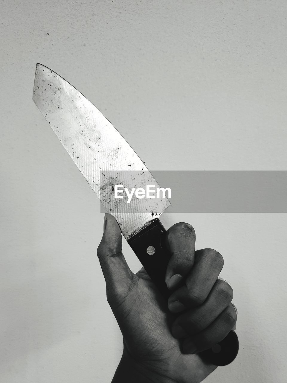Close-up of hand holding knife against white background