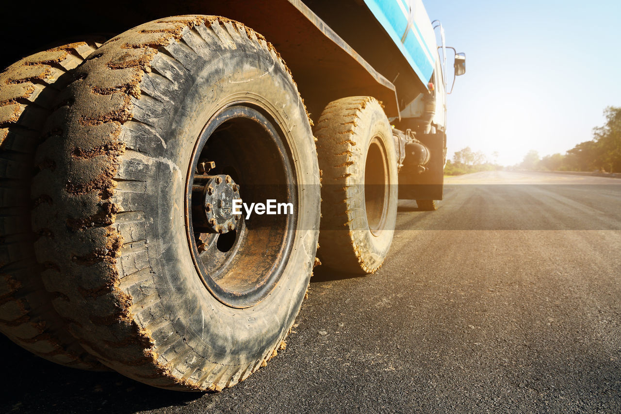 transportation, mode of transportation, wheel, tire, road, land vehicle, sunlight, day, nature, no people, machinery, motor vehicle, outdoors, truck, dirt, clear sky, dirt road, sky, car, construction industry