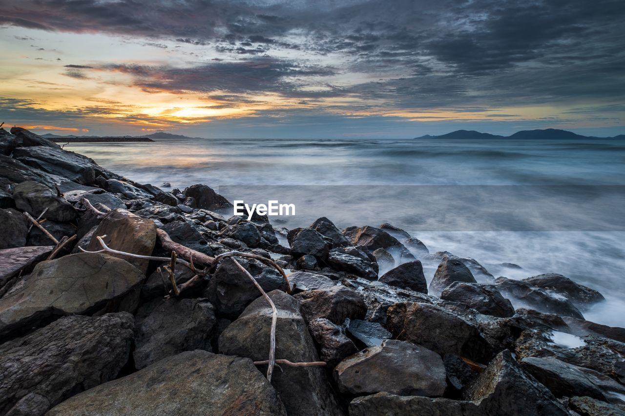 sky, sea, cloud - sky, rock, water, solid, rock - object, sunset, beauty in nature, scenics - nature, beach, horizon over water, horizon, tranquility, land, nature, tranquil scene, motion, no people, outdoors, rocky coastline