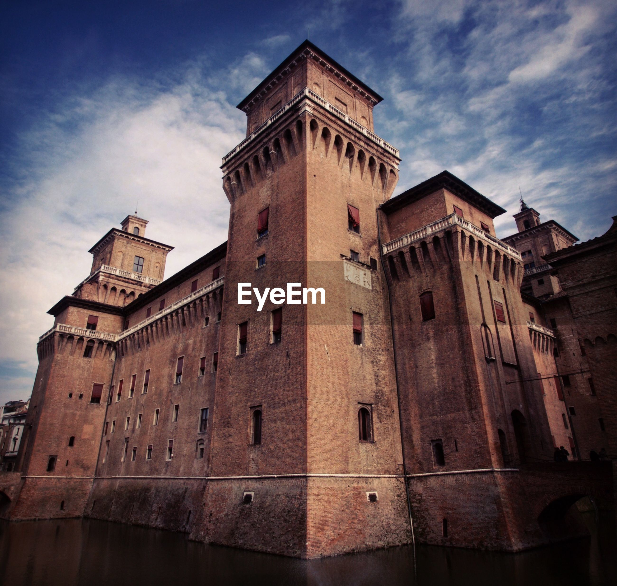 Low angle view of castello estense against cloudy sky