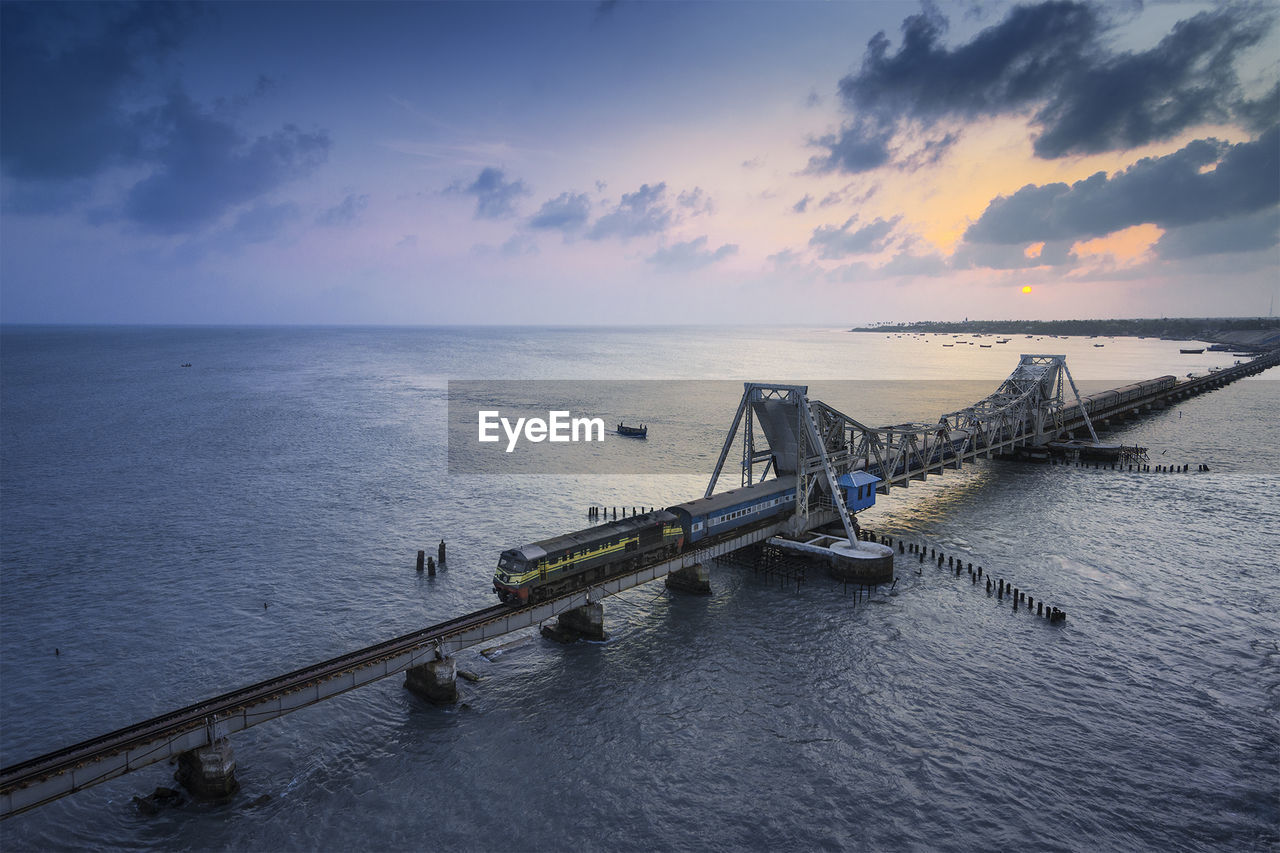 High angle view of railway bridge over sea against sky during sunset