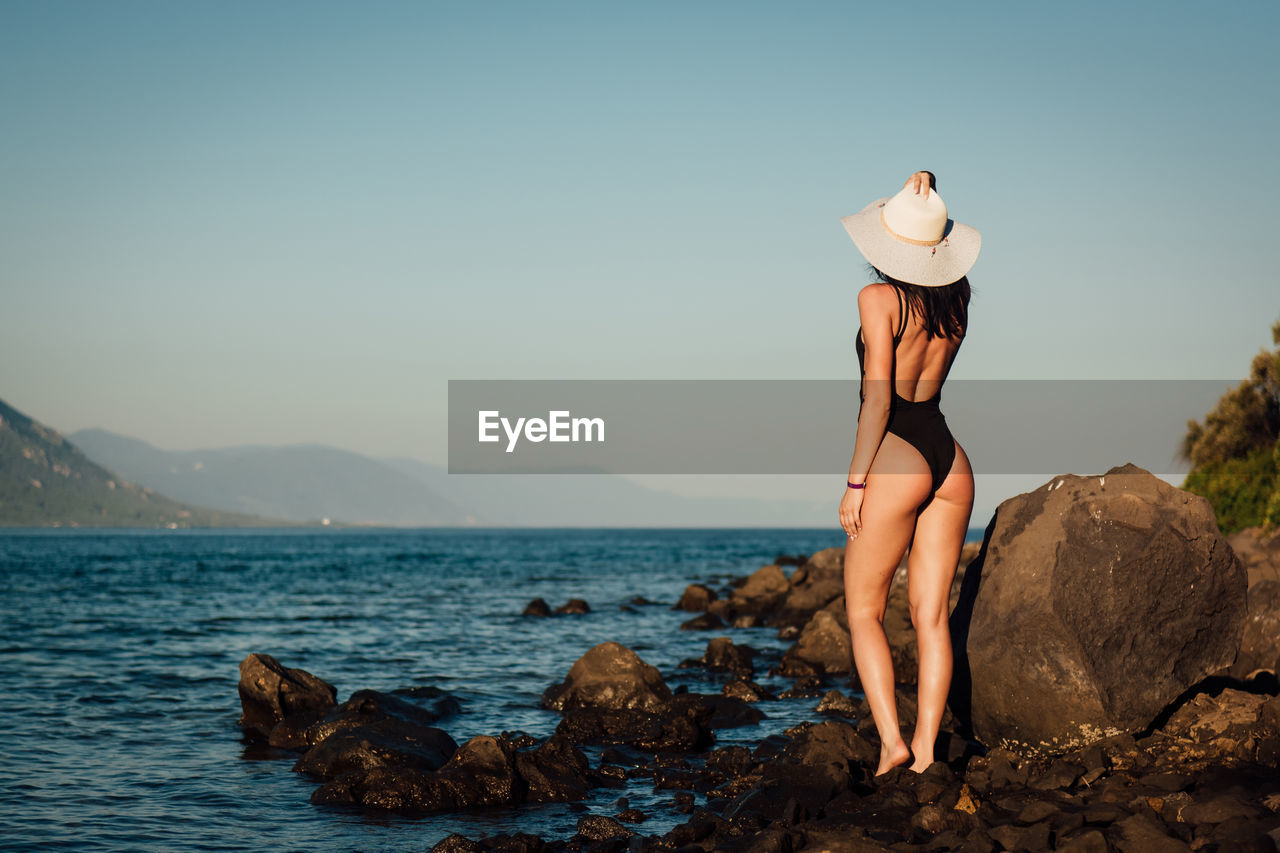 Rear view of sensuous woman standing on rocks at beach against clear sky