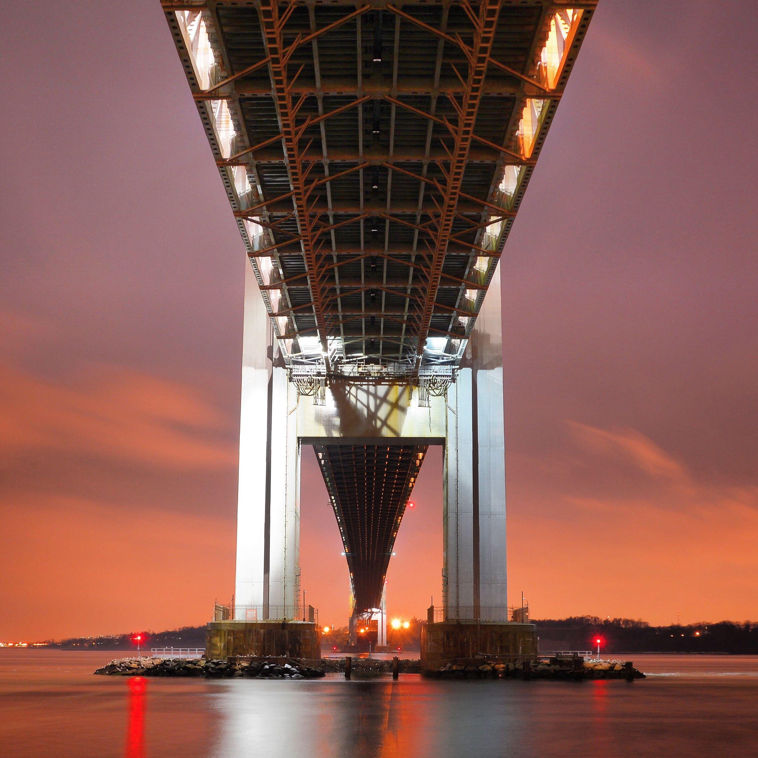 Illuminated suspension bridge over sea at sunset
