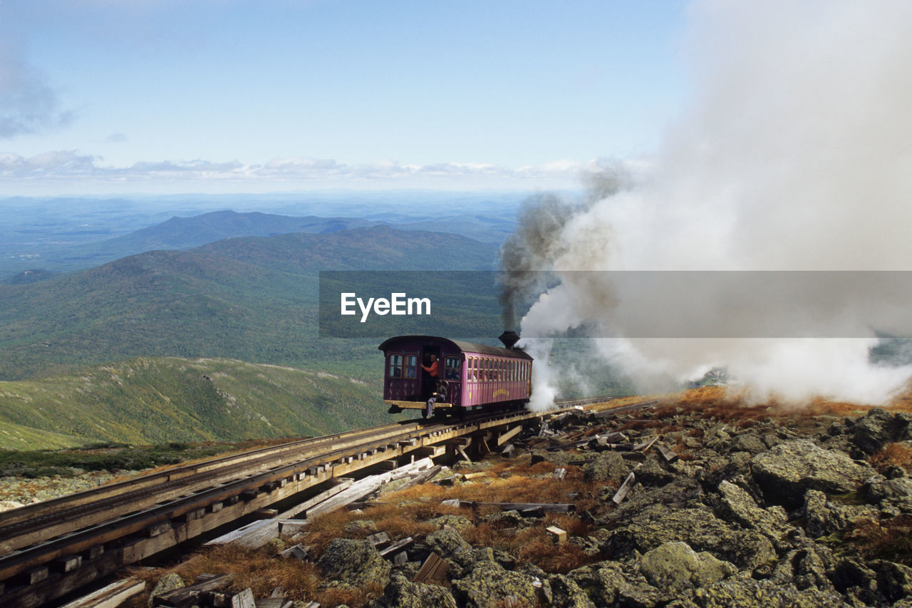 rail transportation, train, train - vehicle, mode of transportation, transportation, mountain, track, railroad track, smoke - physical structure, public transportation, steam train, sky, nature, environment, day, no people, beauty in nature, motion, on the move, land vehicle, outdoors, pollution, air pollution