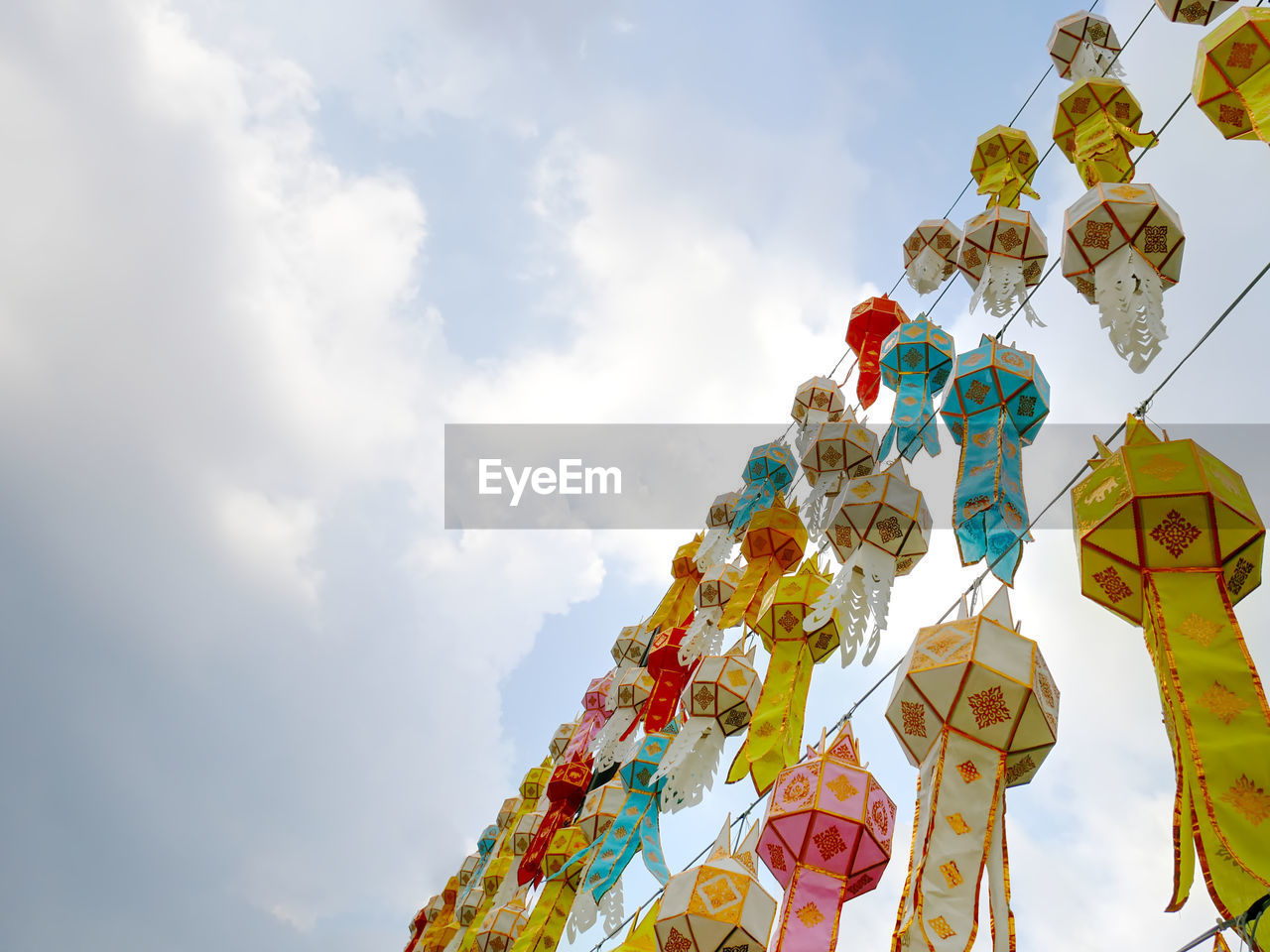 low angle view, sky, cloud - sky, multi colored, no people, decoration, hanging, day, art and craft, creativity, nature, religion, craft, belief, celebration, place of worship, spirituality, outdoors, lighting equipment, ornate