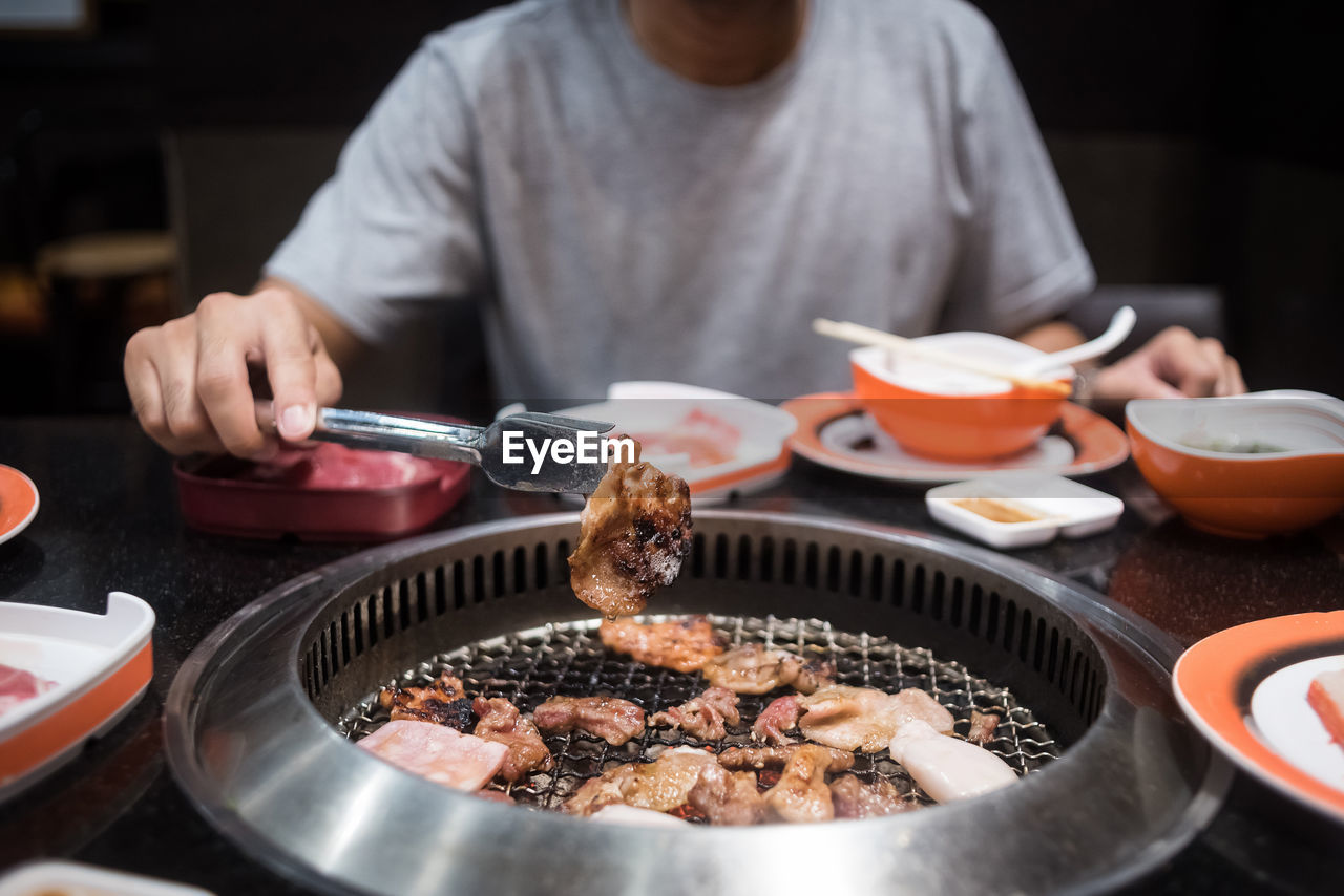 Midsection Of Man Cooking Meat On Barbecue Grill In Restaurant