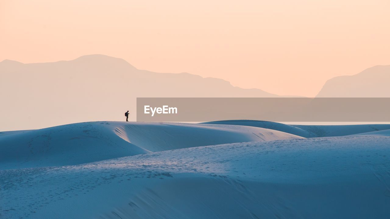 Distant View Of Man Standing On Sand Dunes Against Sky During Sunset