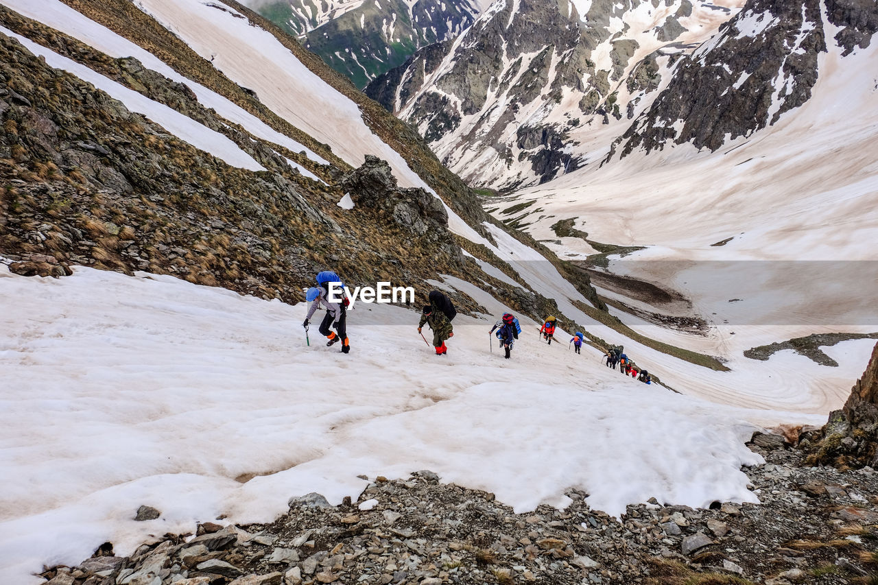 People Skiing On Snowcapped Mountain During Winter