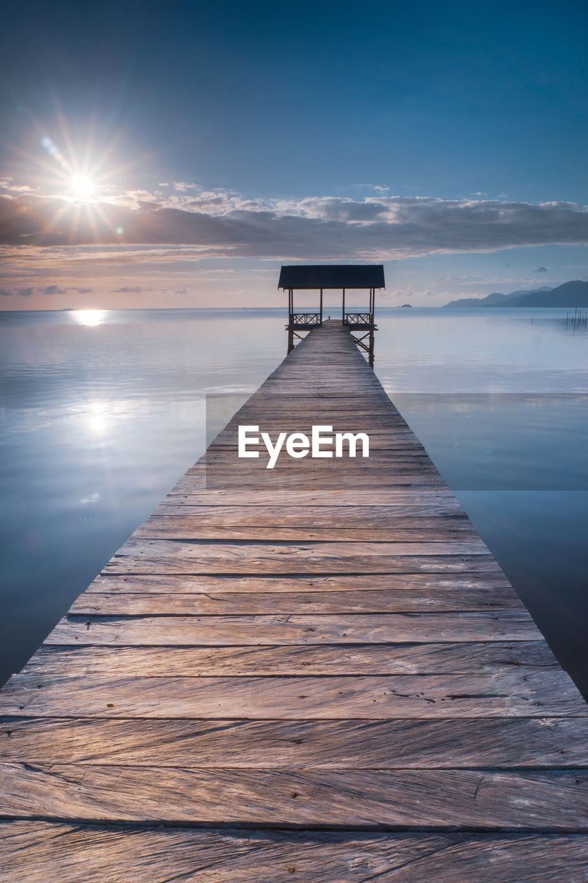 sky, water, scenics - nature, sunset, wood - material, tranquil scene, sea, cloud - sky, beauty in nature, nature, the way forward, direction, tranquility, pier, no people, horizon over water, sun, idyllic, built structure, diminishing perspective, outdoors, long