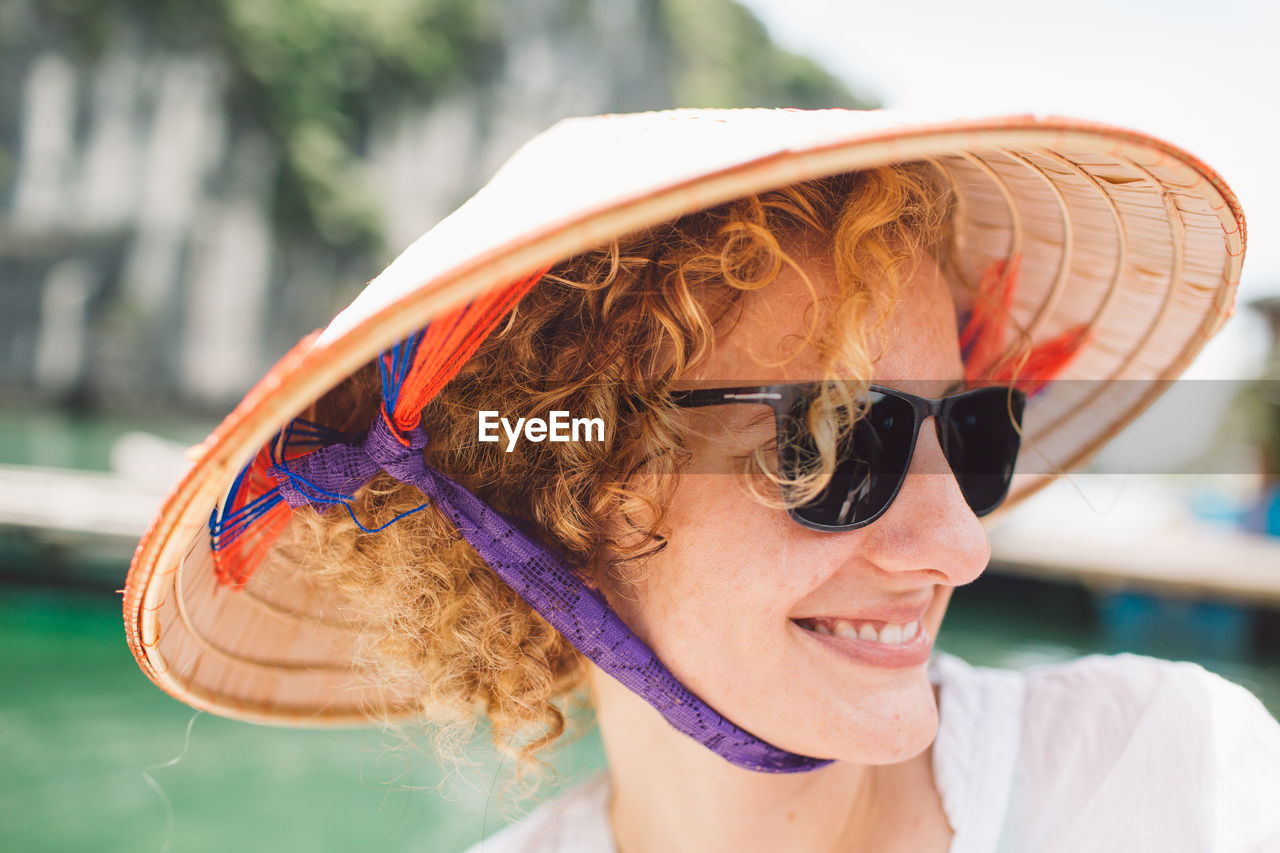 Close-up of smiling woman wearing sunglasses and hat