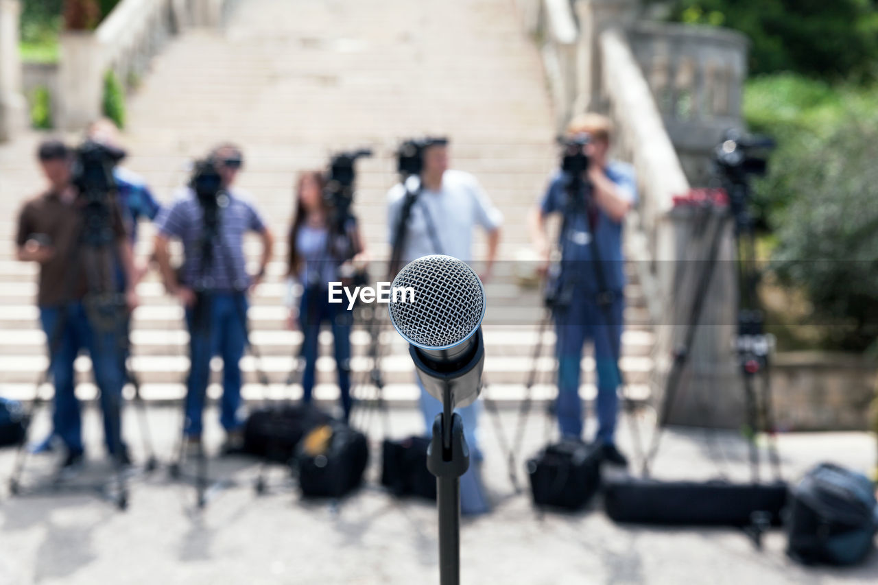Close-Up Of Microphone Against People Photographing Outdoors