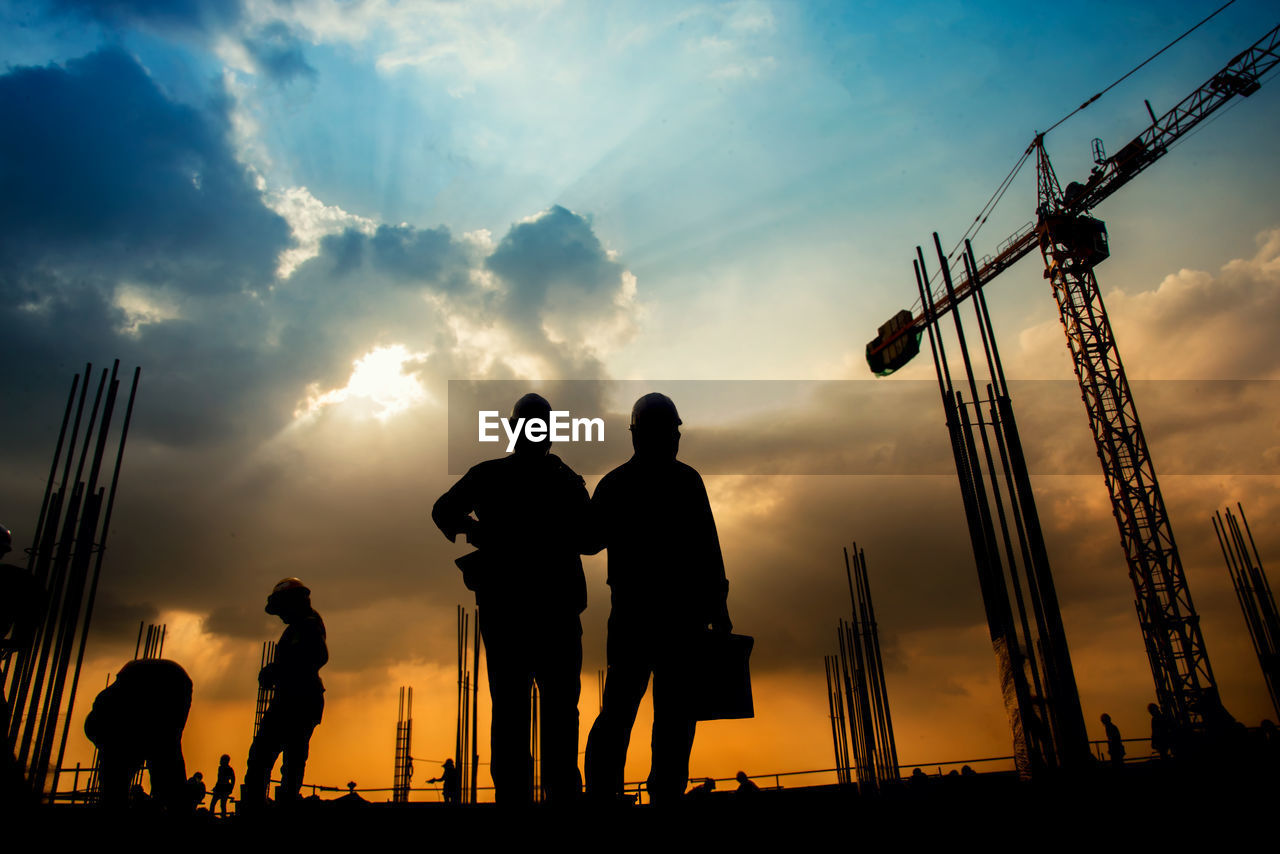 Silhouette workers working at construction site against cloudy sky during sunset