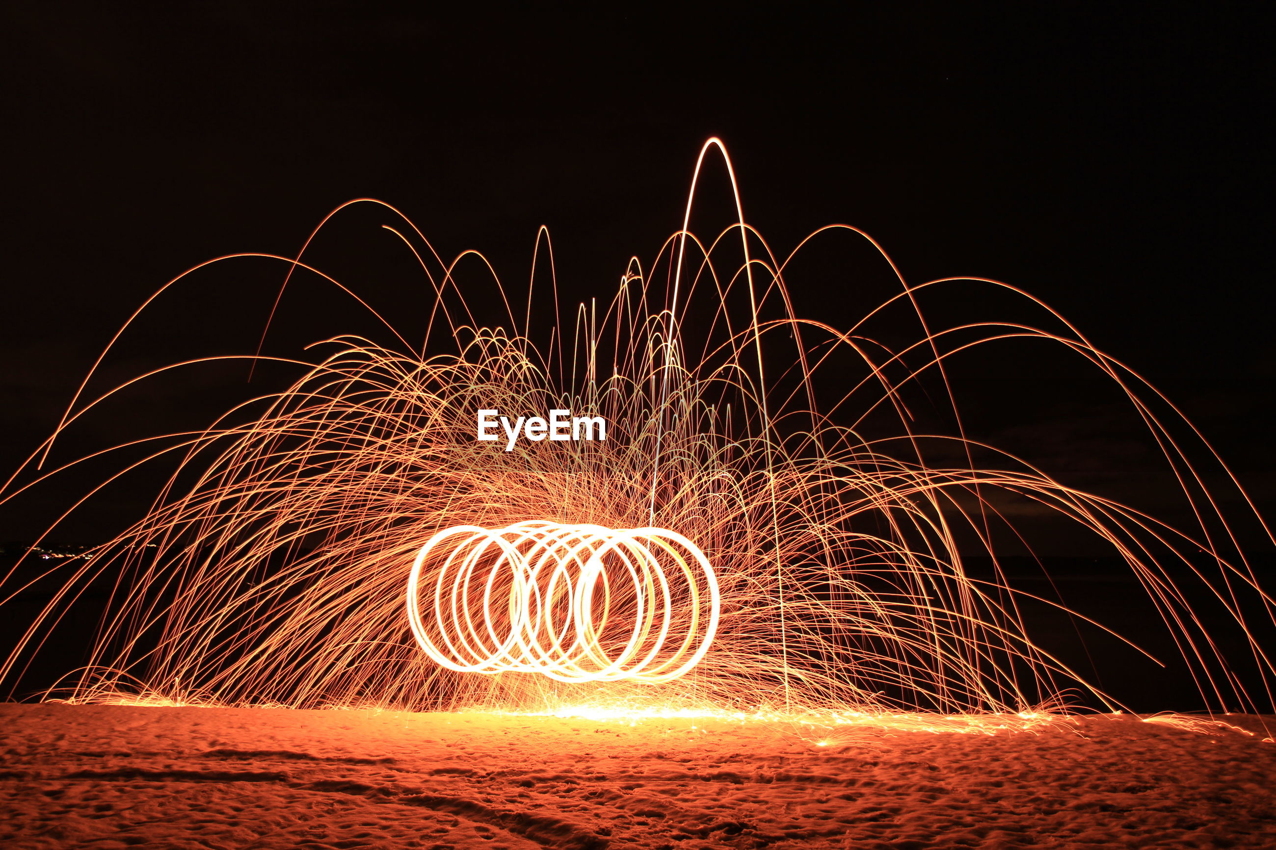 Illuminated wire wool at beach against sky