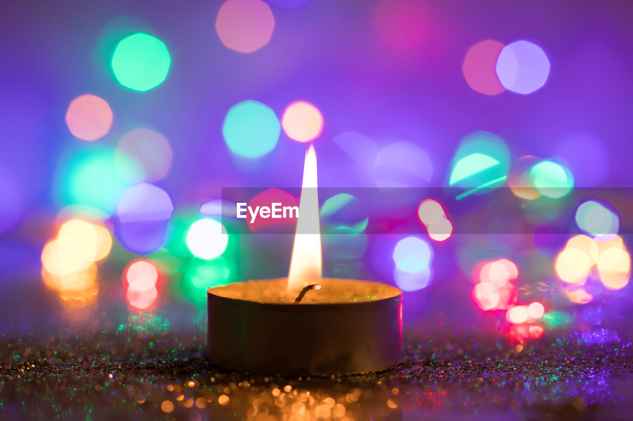 illuminated, glowing, lens flare, no people, heat - temperature, close-up, burning, flame, multi colored, fire, celebration, selective focus, night, candle, lighting equipment, defocused, fire - natural phenomenon, light - natural phenomenon, indoors, focus on foreground