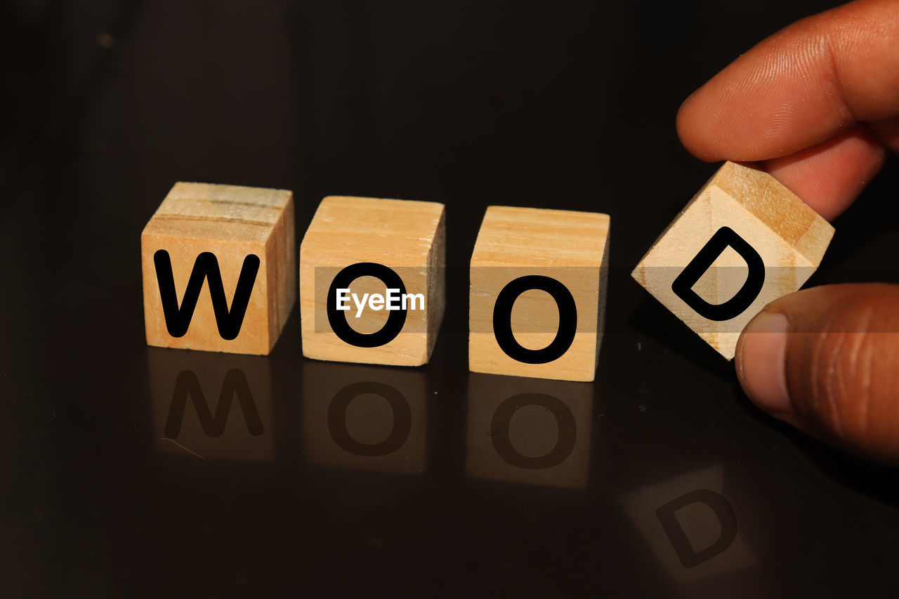 Cropped hand with wood text on toy blocks against black background