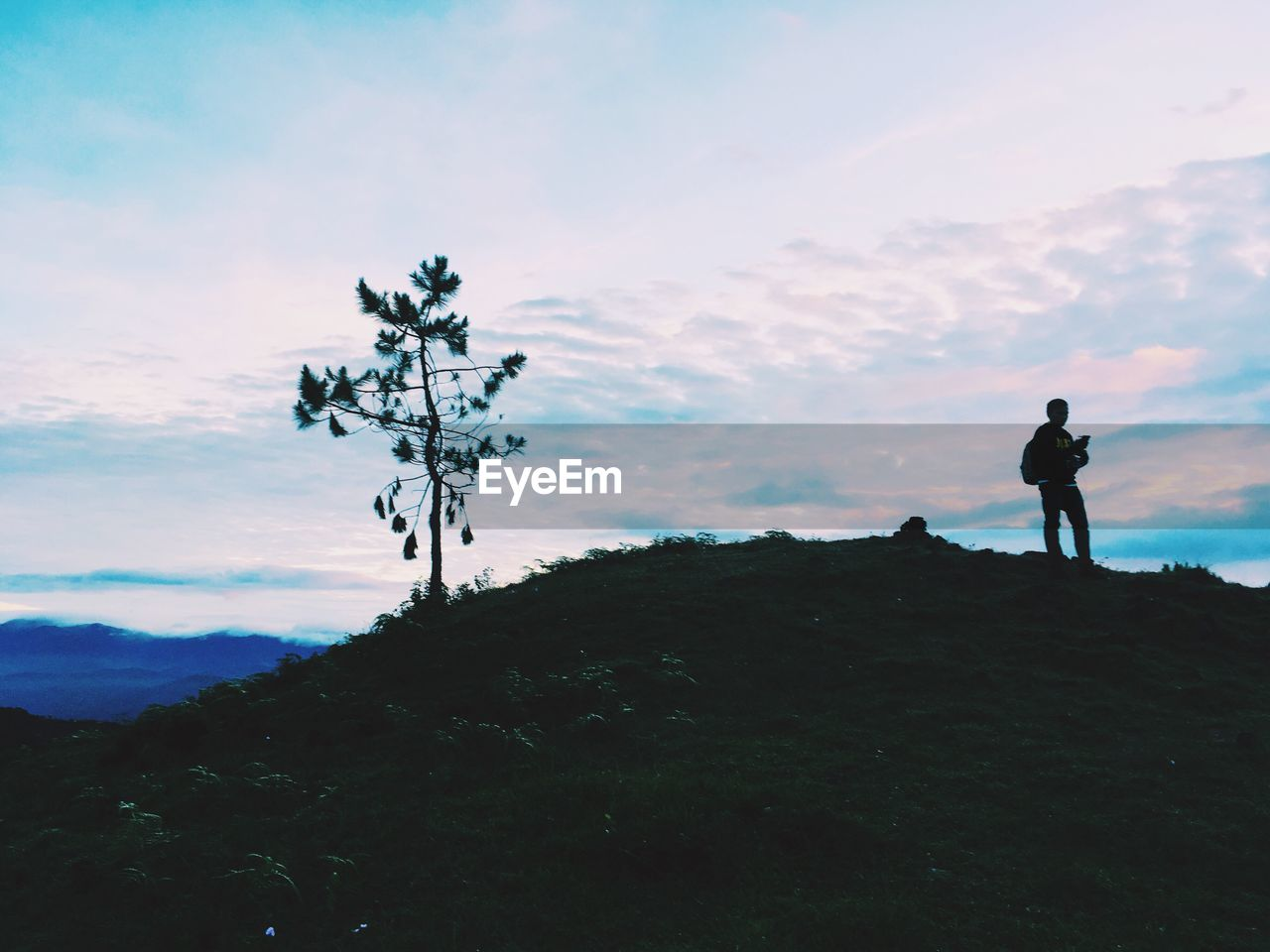 silhouette, adventure, hiking, mountain, nature, solitude, outdoors, tranquil scene, one person, rock - object, scenics, sky, standing, real people, landscape, beauty in nature, tranquility, cloud - sky, men, full length, leisure activity, sunset, day, vacations, tree, people