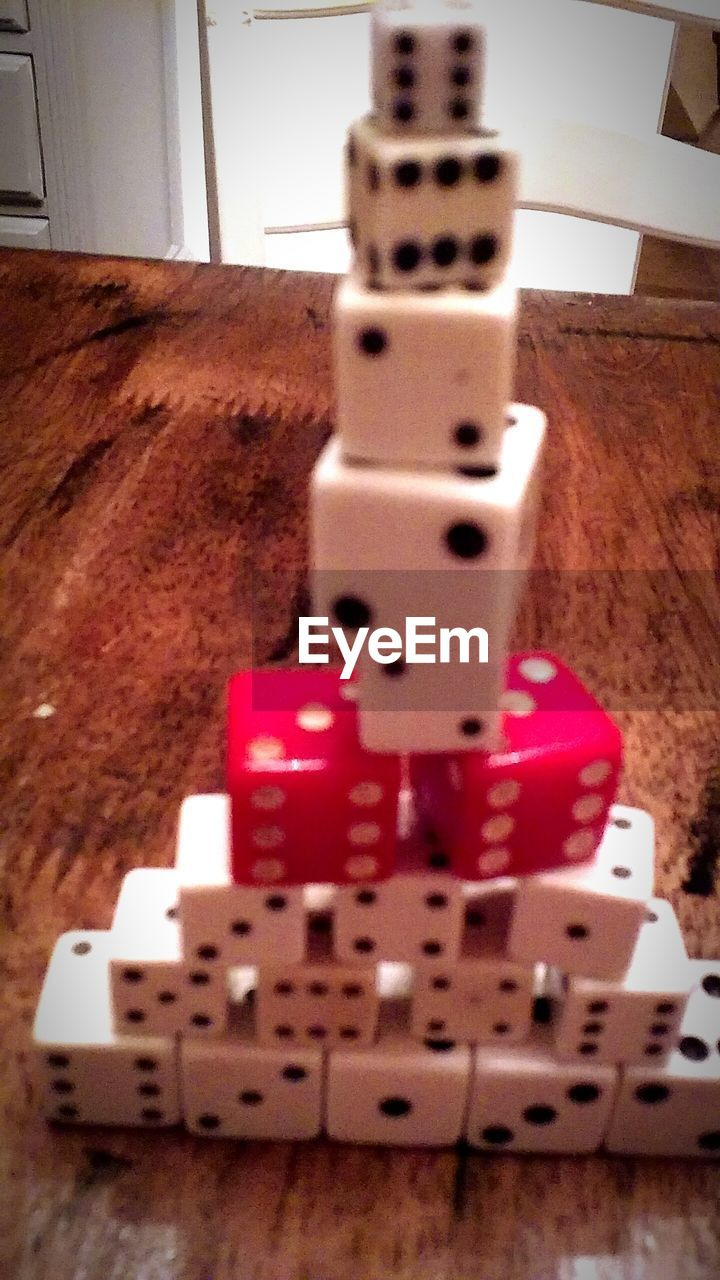 indoors, close-up, no people, table, red, still life, selective focus, technology, relaxation, focus on foreground, stack, arts culture and entertainment, high angle view, wood - material, white color, connection, equipment, wood, toy, leisure games