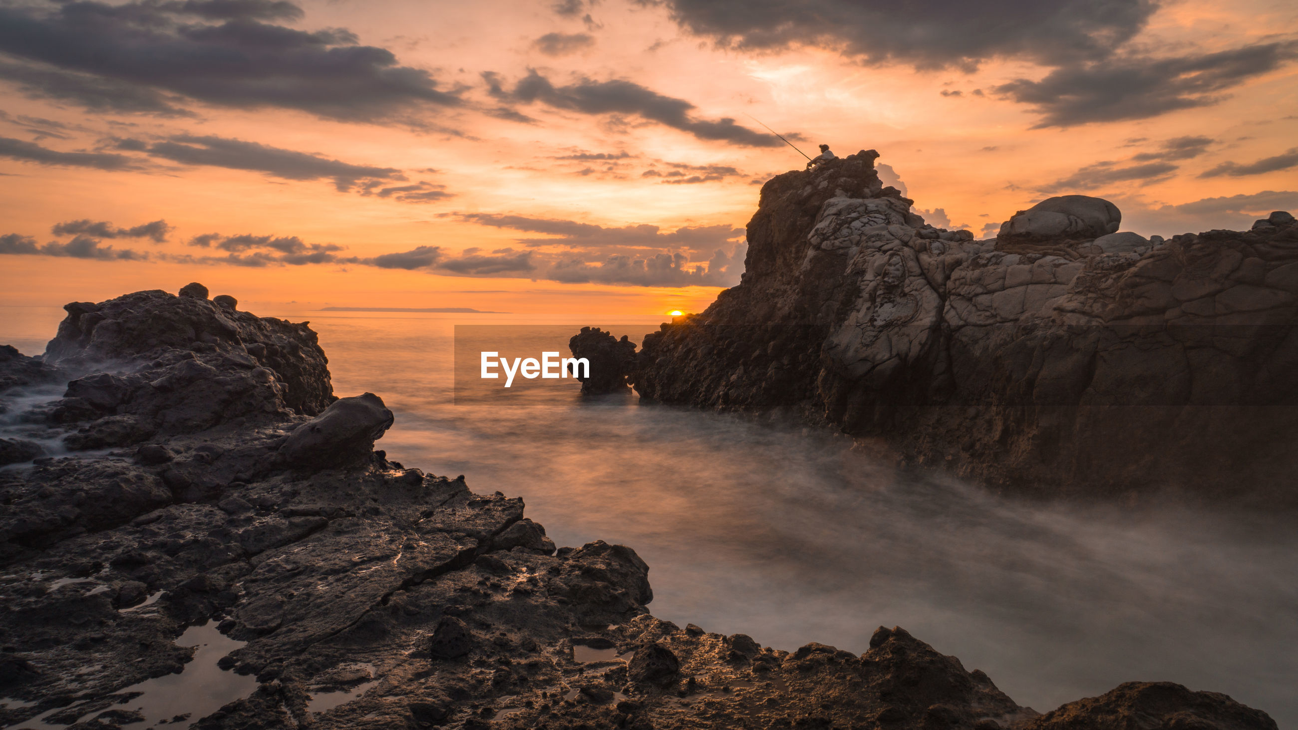 SCENIC VIEW OF ROCK FORMATION IN SEA AGAINST SKY DURING SUNSET