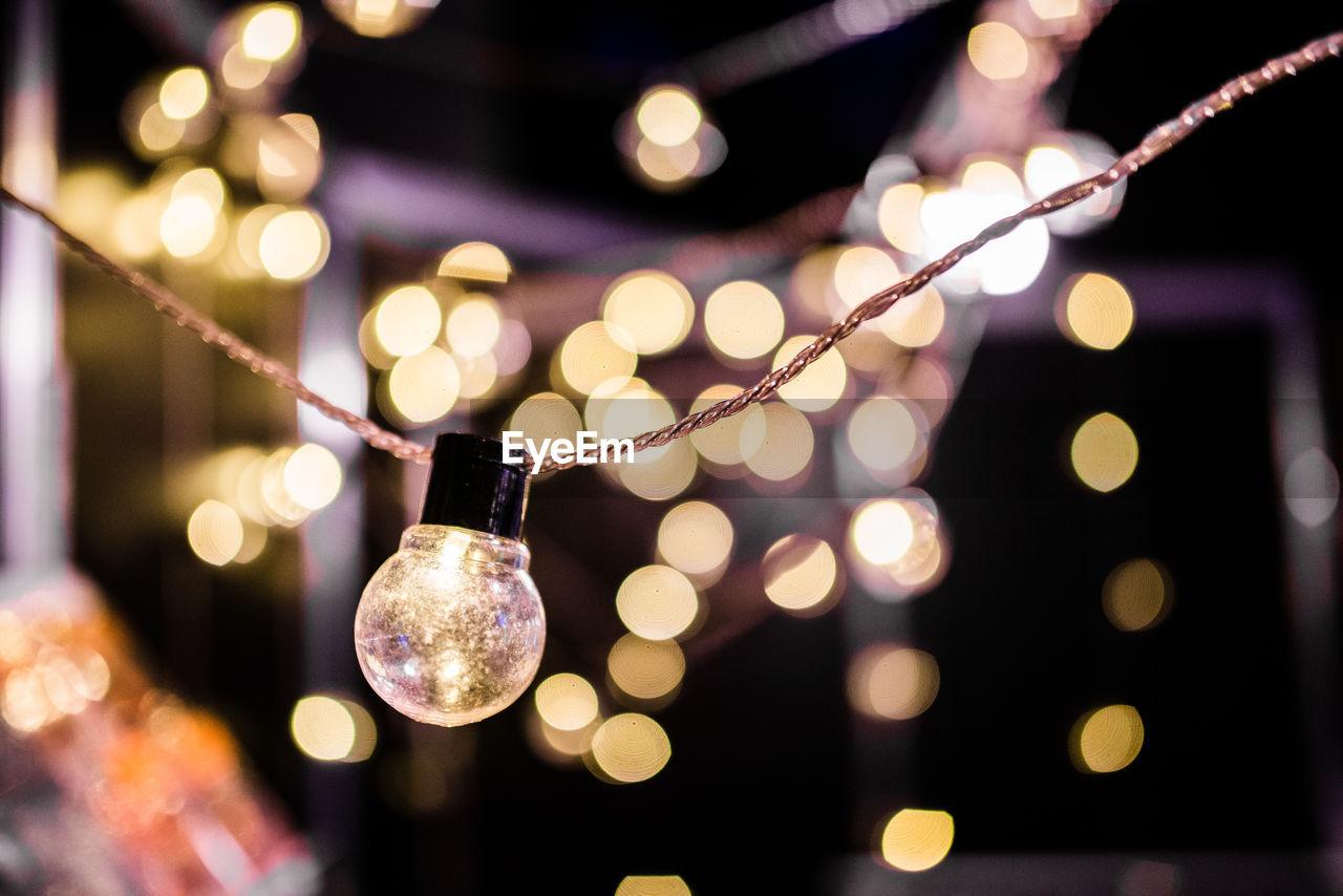Close-Up Of Illuminated Light Bulb Against Defocused Lights