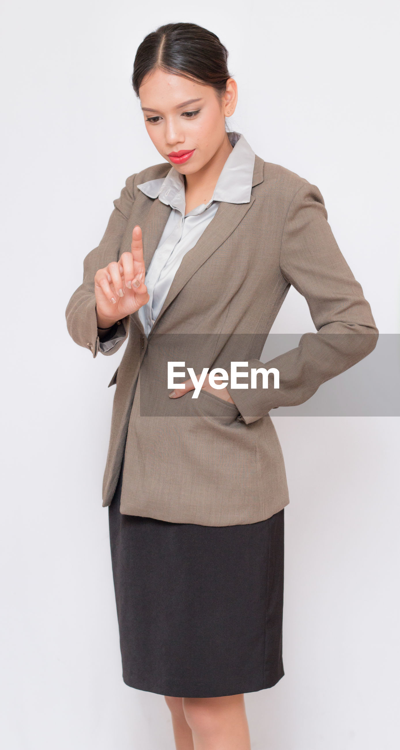 Businesswoman with hand in pocket pointing against white background