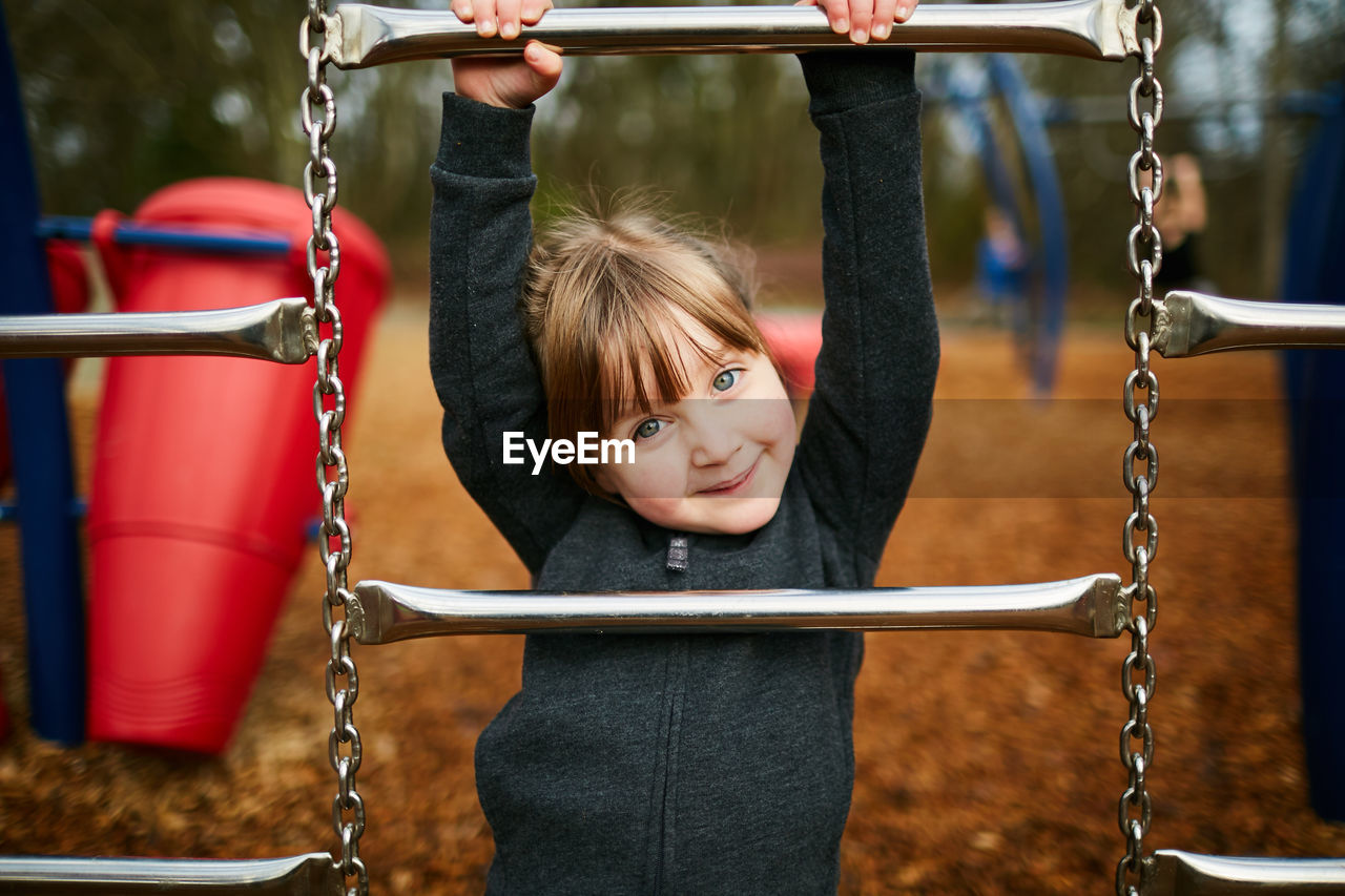 childhood, child, playground, chain, swing, one person, smiling, girls, portrait, looking at camera, emotion, women, happiness, females, outdoor play equipment, focus on foreground, real people, innocence, hair, hairstyle, bangs, jungle gym