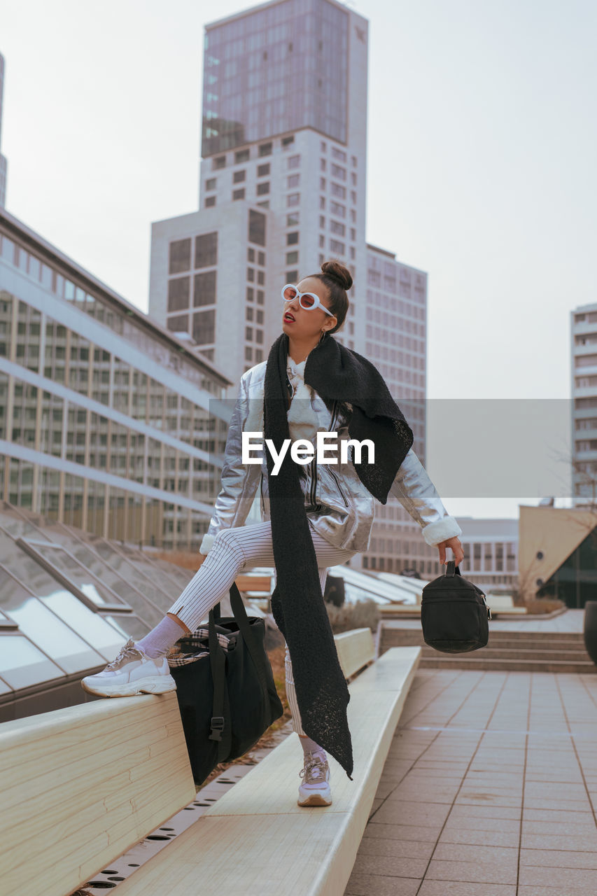 building exterior, architecture, built structure, city, one person, young adult, building, real people, office building exterior, young men, full length, lifestyles, day, sky, office, casual clothing, leisure activity, young women, adult, skyscraper, outdoors