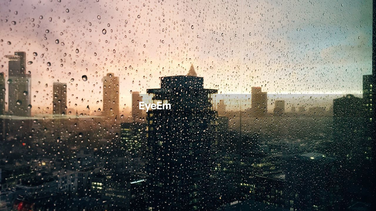 Waterdrops on glass against silhouette buildings