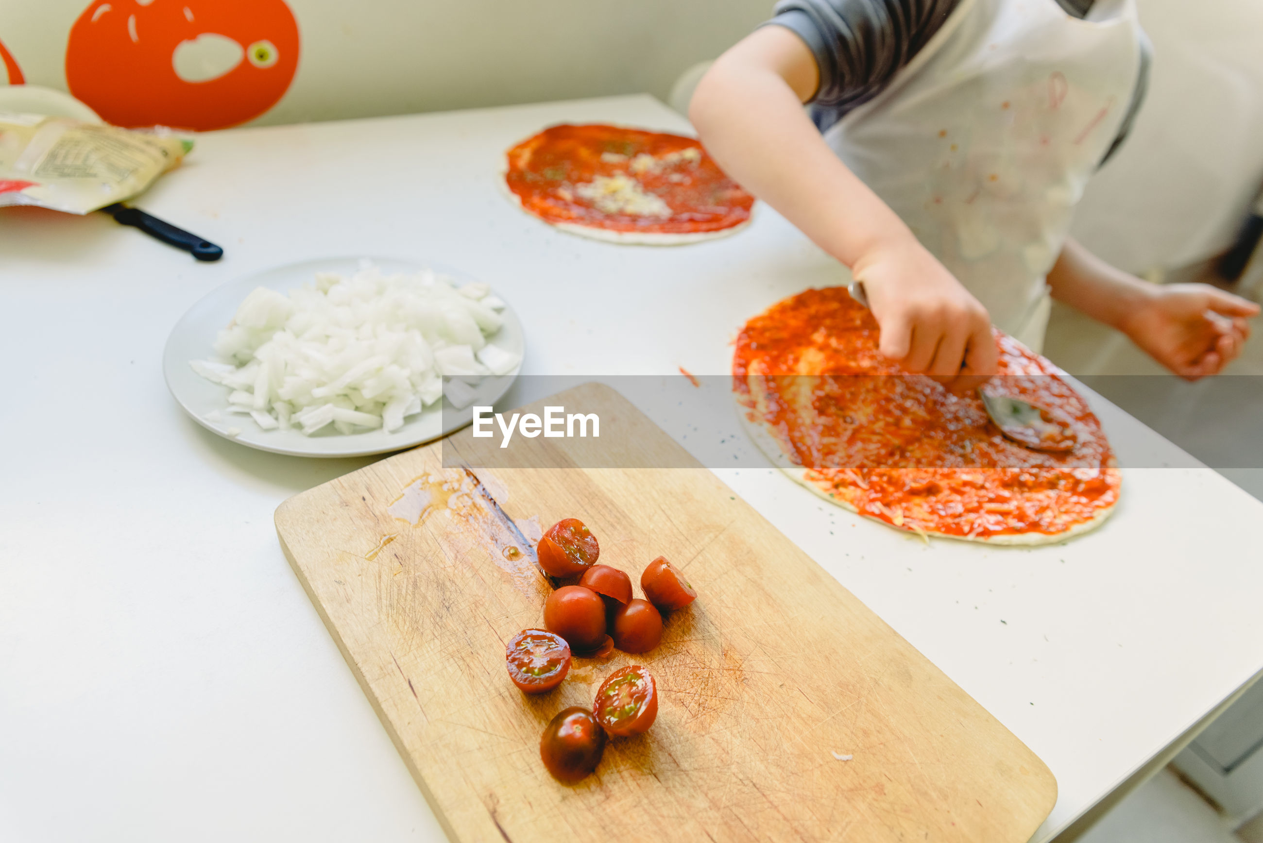 Midsection of boy making pizza on table at home