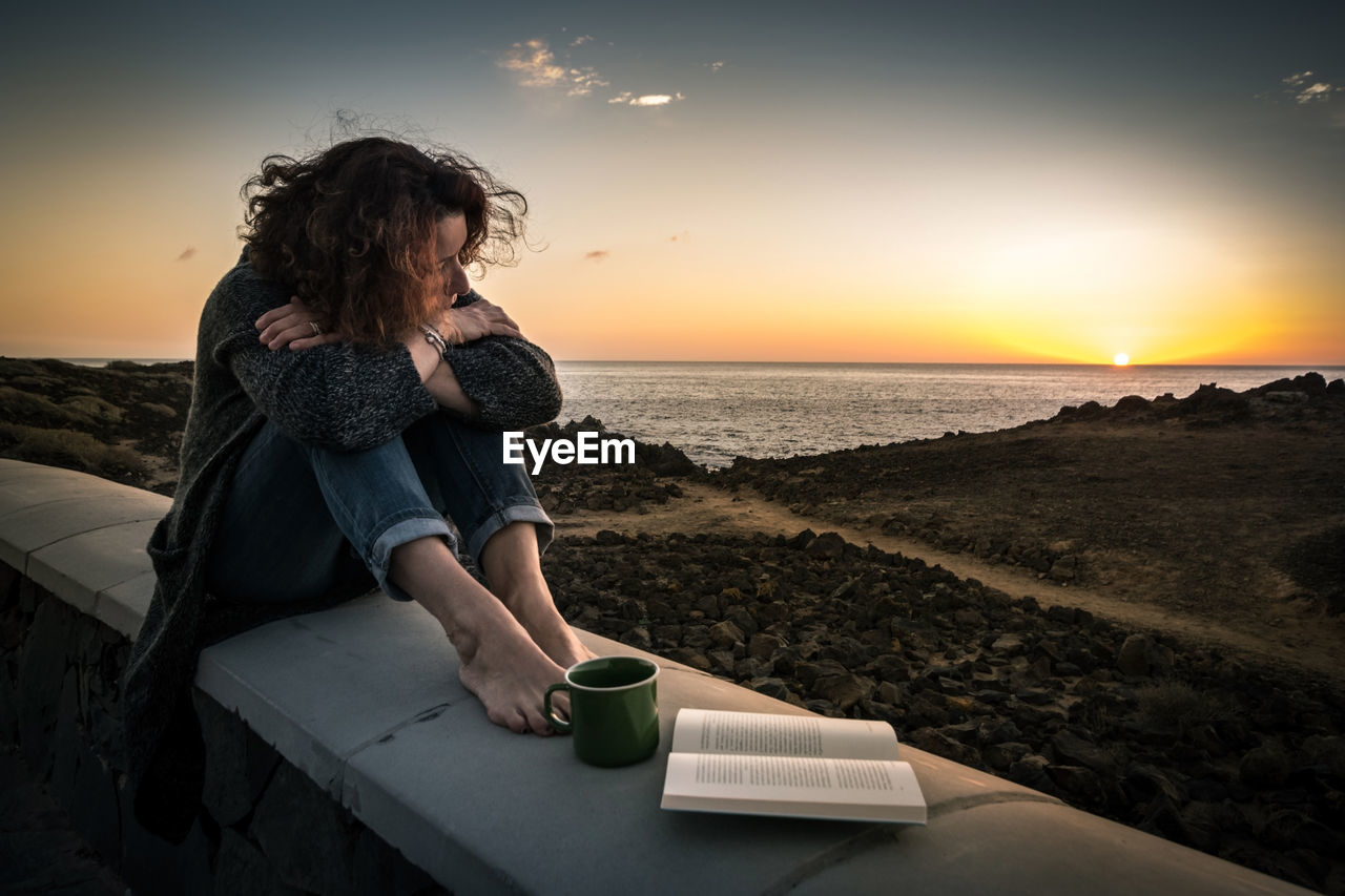Woman Sitting By Cup Of Coffee And Book On Building Terrace Against Sky