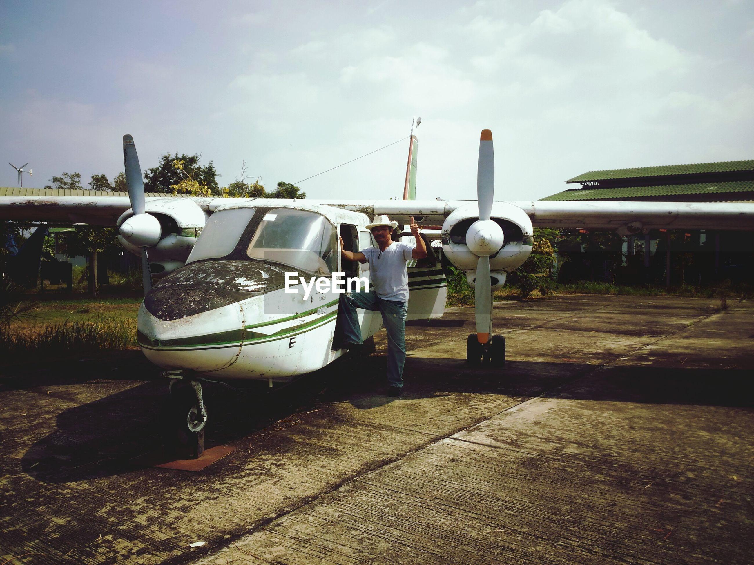 Full length of man standing in airplane against sky