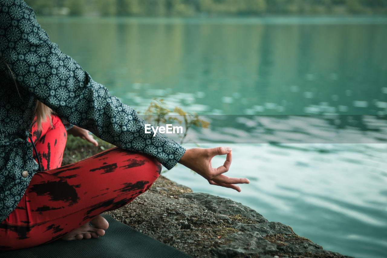 Low Section Of Woman Doing Yoga On Rock At Lake