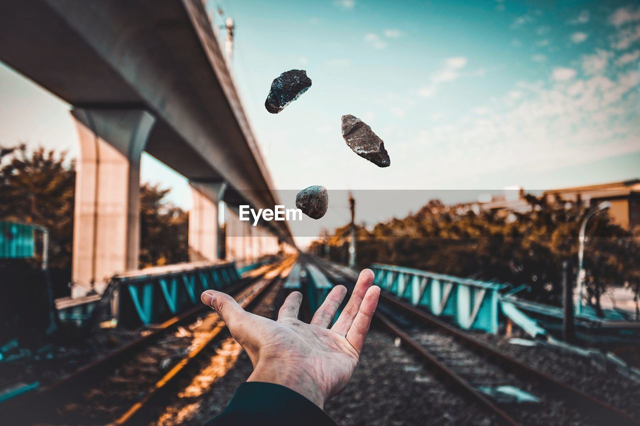 Close-Up Of Hand On Railroad Track Against Sky