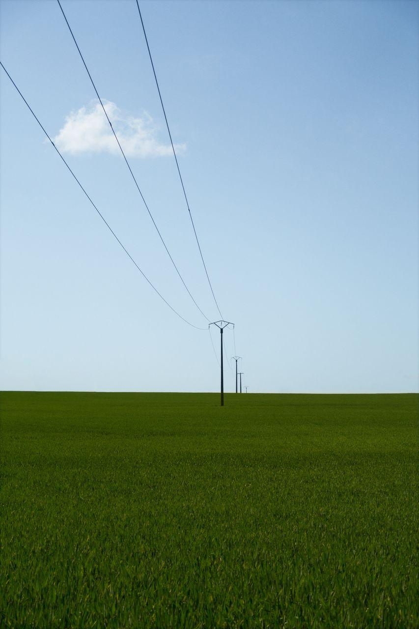 ELECTRICITY PYLON ON FARM AGAINST SKY